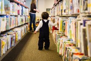 little boy walking aisles in library