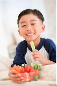 little boy eating raw vegetables