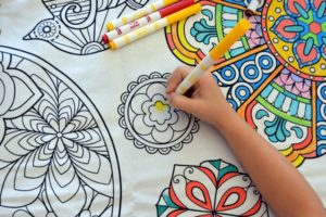 girl coloring mandala tablecloth with markers