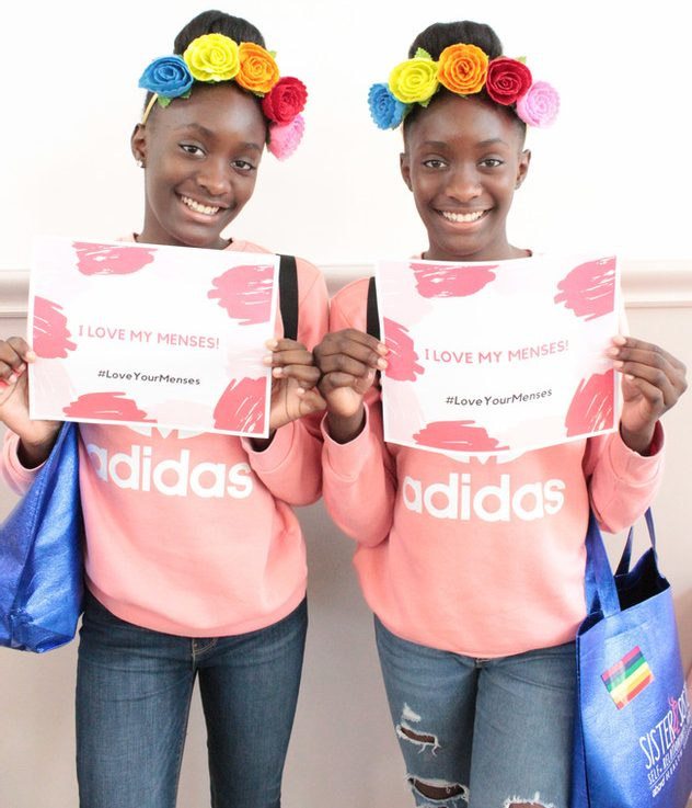 two girls holding certificates from love your menses