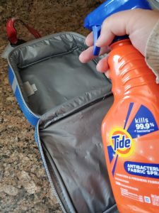 spraying a sanitizing spray on a lunch bag
