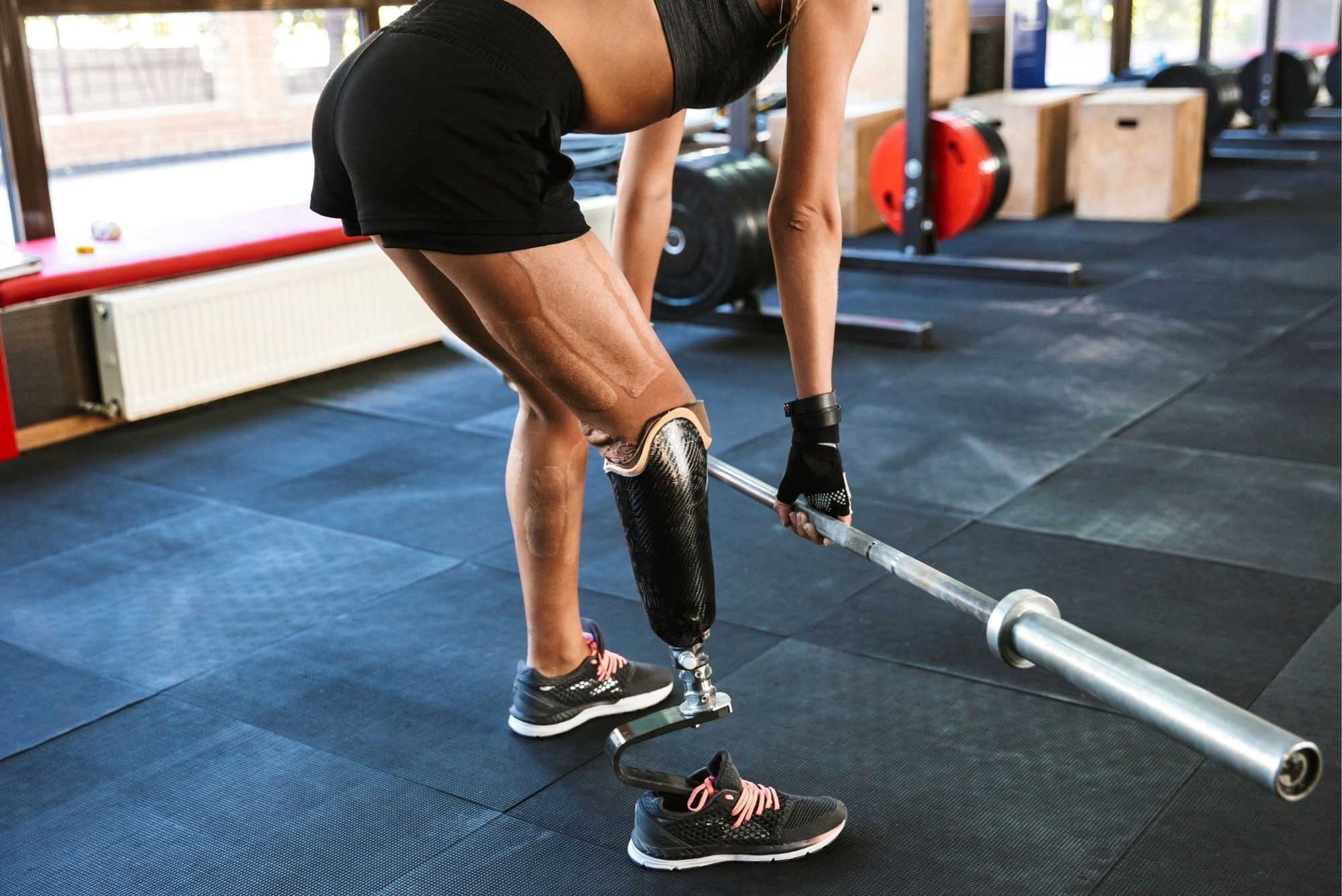 A woman with a prosthetic limb lifts weights at the gym